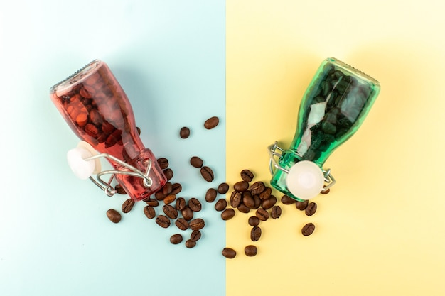 Вид сверху коричневые семена кофе внутри цветных стеклянных банок на сине-желтой поверхности напиток из кофейных зерен цветная фотография Бесплатные Фотографии