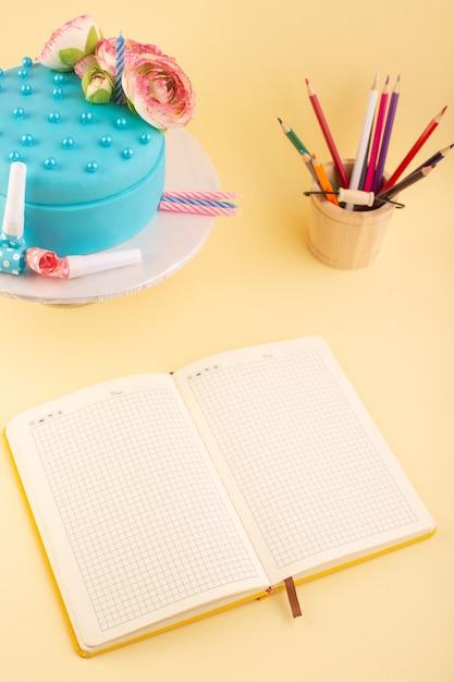 トップビューケーキと黄色の机の誕生日お祝いケーキパーティーで色とりどりの鉛筆のコピーブック 無料写真