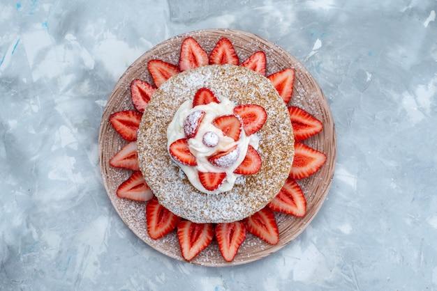 青灰色の背景にプレート内のクリームと新鮮な赤いイチゴの平面図ケーキスライス 無料写真