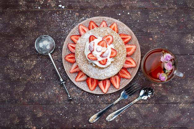 Кусочек торта с кремом и свежей красной клубникой внутри тарелки с чаем на темном фоне, вид сверху Бесплатные Фотографии