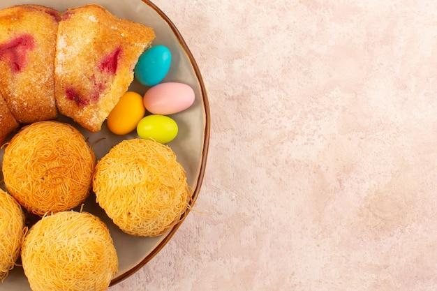 Вид сверху на кусочки вишневого торта с конфетами и печеньем на розовом настольном кексе Бесплатные Фотографии