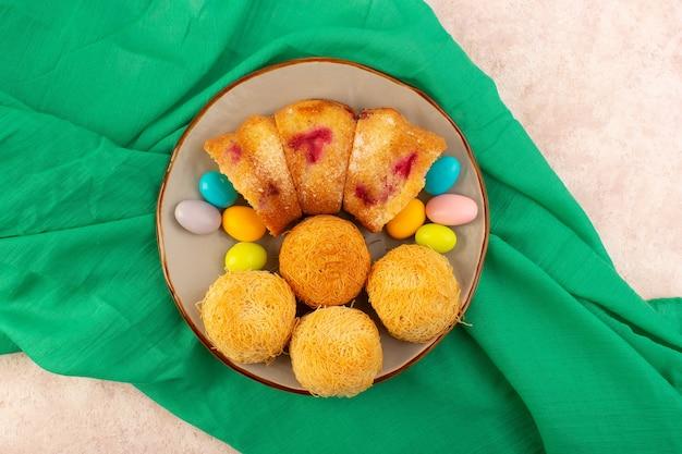 Вид сверху кусочки вишневого торта с конфетами и печеньем на розовом бисквитном пироге Бесплатные Фотографии