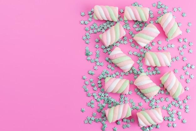 Вид сверху жевательного зефира, раскрашенного вместе с зелеными конфетами в форме звезды, все на розовом столе, сладкие леденцы Бесплатные Фотографии