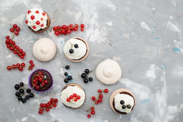 白い背景の上のケーキビスケットドーナツチョコレートのフルーツで設計されたドーナツクリームとトップビューチョコレートケーキ 無料写真