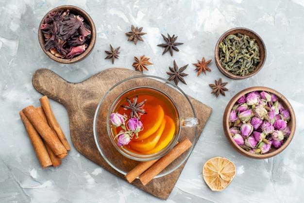 トップビューシナモンとドライレモンスライスと一緒に花とライトデスクドライフルーツの花のお茶 無料写真