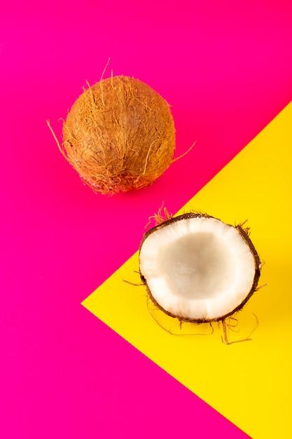 ピンクと黄色に分離された平面図ココナッツスライスと全体の乳白色の新鮮なまろやか 無料写真