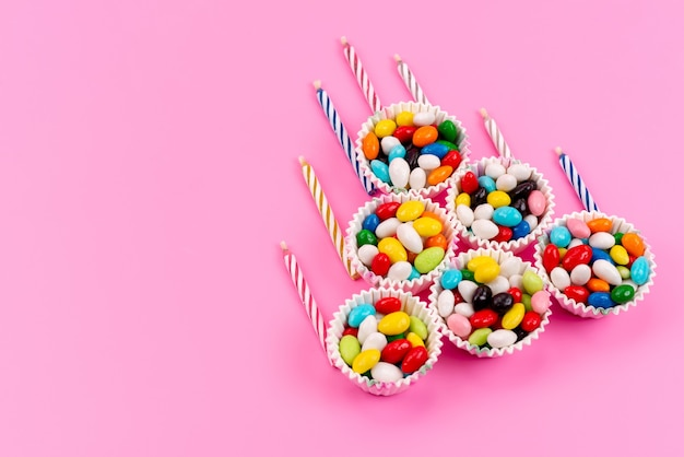 ピンクのキャンドルと一緒に紙のパッケージ内のトップビューカラフルなキャンディー 無料写真