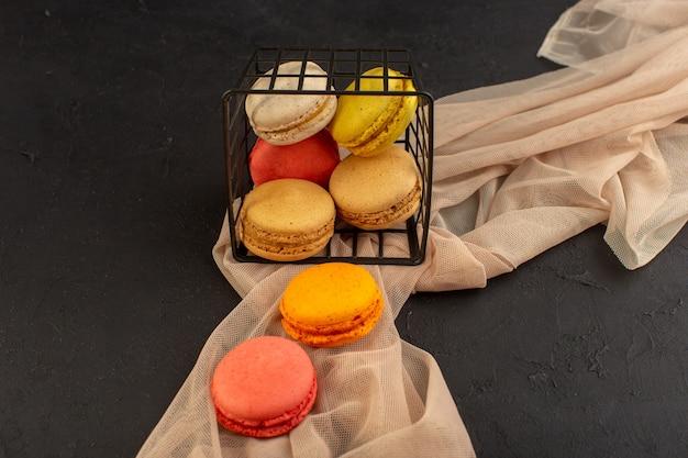 Вид сверху красочные французские макароны вкусные и запеченные внутри корзины на темном столе, торт, печенье, печенье, сахар Бесплатные Фотографии