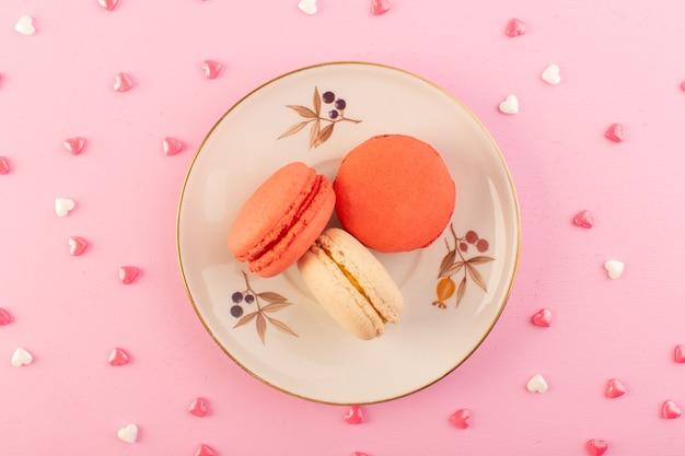 ピンクのデスクケーキビスケット砂糖甘いプレート上の平面図カラフルなフランスのマカロン 無料写真