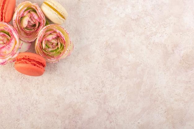 ピンクのデスクケーキの甘い砂糖のビスケットにしおれたバラとトップビューカラフルなフランスのマカロン 無料写真
