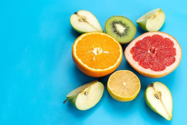 平面図のカラフルな果物の組成は青、果物のカラー画像でまろやかで新鮮な果物をスライス 無料写真