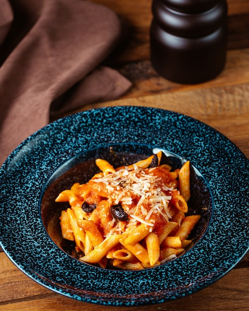 Вид сверху приготовленная итальянская паста с соусом на коричневом деревянном столе паста готовить еду Бесплатные Фотографии