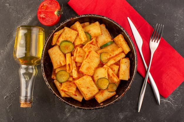 Вид сверху приготовленная итальянская паста с томатным соусом и огурцом внутри сковороды Бесплатные Фотографии