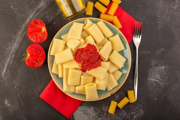 Вид сверху приготовленная итальянская паста с томатным соусом внутри тарелки с оливковым маслом Бесплатные Фотографии