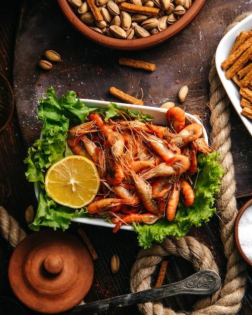 Вид сверху приготовленные креветки с зеленым салатом и лимоном на деревянном столе еда еда морепродукты Бесплатные Фотографии