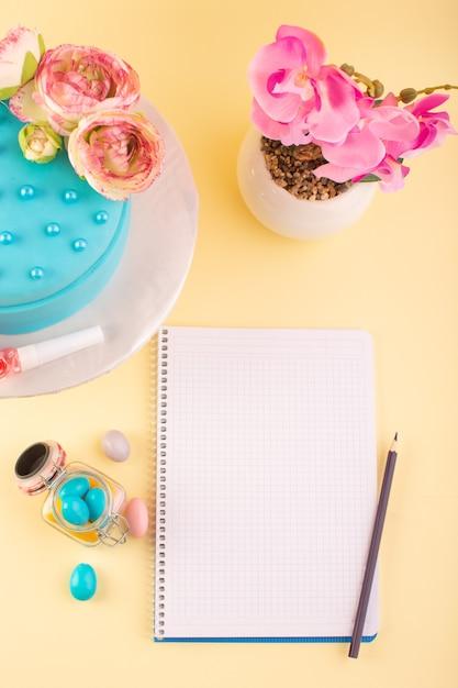 黄色の机の誕生日お祝いパーティーのトップビューコピーブックとキャンディーと花のケーキ 無料写真