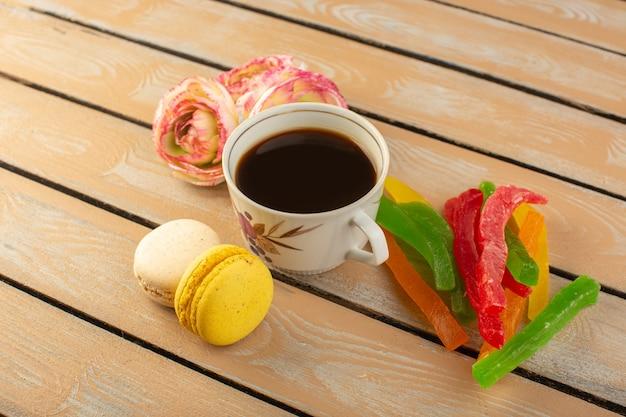 トップビューコーヒーカップホットで強いフランスのマカロンの花とクリーム色の素朴なデスクにマーマレードを飲むコーヒー写真甘いビスケット 無料写真