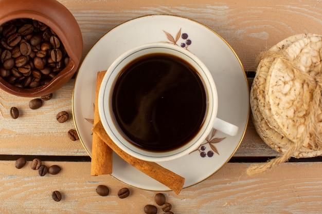 新鮮で茶色のコーヒーシードシナモンとクリームの素朴なデスクのコーヒーシードドリンク写真穀物のクラッカーとホットで強いコーヒーのトップビューカップ 無料写真