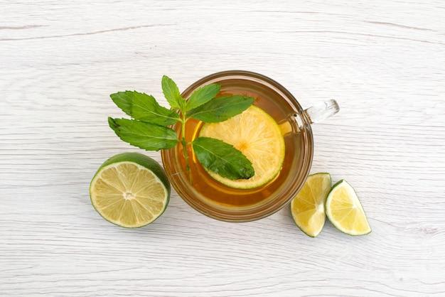 Чашка чая сверху с зеленым лимоном и мин на белом, фруктовый чай с водой Бесплатные Фотографии