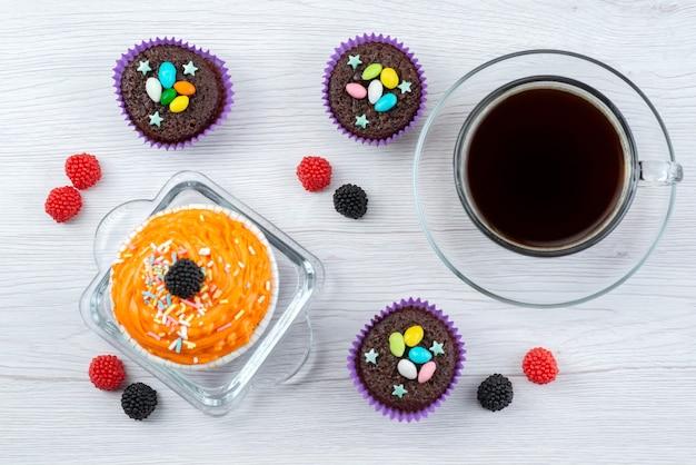 Вид сверху восхитительных пирожных внутри фиолетовых форм вместе с чашкой чая на белых конфетах конфетного цвета Бесплатные Фотографии