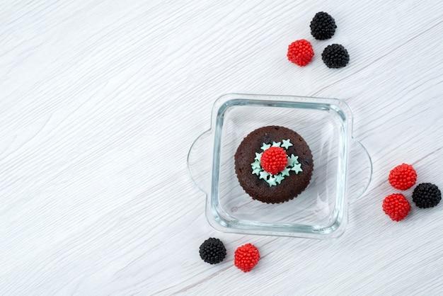 Вид сверху восхитительного коричневого цвета внутри фиолетовой формы вместе со свежими ягодами на белых конфетах конфетного цвета Бесплатные Фотографии