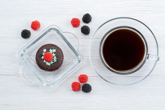 キャンディーカラーの白のお菓子にお茶を入れた紫色のフォルムの中の茶色のトップビュー 無料写真