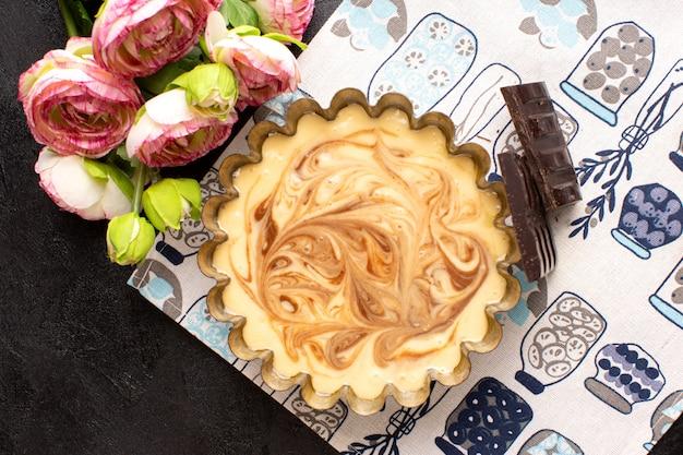 Вид сверху вкусный кофейный торт сладкий шоколадный вкусный кондитерский торт сладкий вместе с розами на темном столе Бесплатные Фотографии