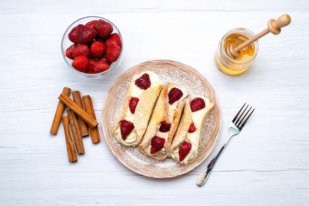 白い背景のケーキフルーツにシナモンと蜂蜜と一緒にクリームとイチゴの平面図おいしいエクレア 無料写真
