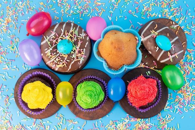 Вид сверху, пончики и пирожные, вкусные и шоколадные, вместе с конфетами на синем, конфетном бисквитном цвете Бесплатные Фотографии