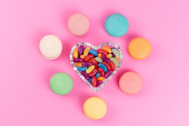 Вид сверху французские макароны круглые, выложенные вместе с жевательными конфетами на розовом, сладком сладком пироге Бесплатные Фотографии