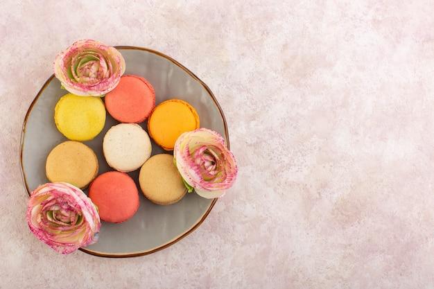 トップビューピンクのテーブルケーキビスケットシュガー甘いプレート内の花とフランスのマカロン 無料写真