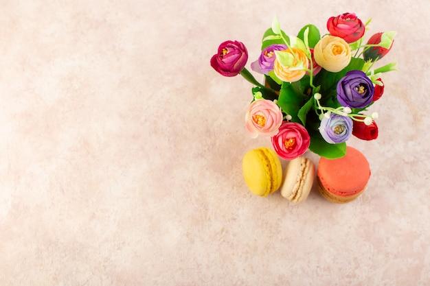 トップビューピンクのテーブルケーキビスケット砂糖甘い花とフランスのマカロン 無料写真
