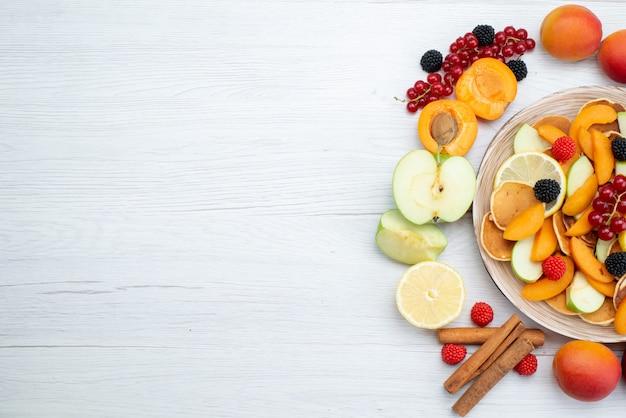 トップビューの新鮮な果物のカラフルで熟した木製の机と白い背景の果物色の食品写真 無料写真