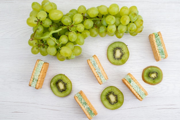 トップビューフレッシュグリーンブドウサワージューシーでまろやかな、白い背景のフルーツ熟した植物のクッキーとキウイ 無料写真