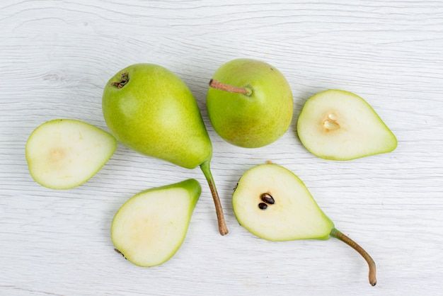 トップビューの新鮮な緑色の洋ナシのスライスと全体の白い背景の果物の色 無料写真