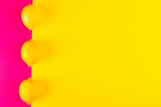 トップビューフレッシュイエローレモン熟したジューシーなまろやかな全体がピンクイエローの背景果物柑橘類夏に並ぶ 無料写真