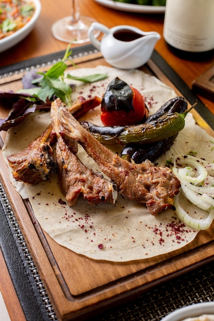 Вид сверху жареные мясные кости с жареными овощами и соусом на столе еда обед ужин ресторан Бесплатные Фотографии