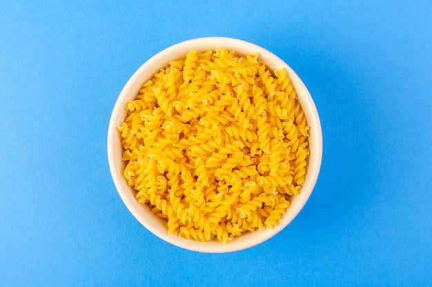 Вид сверху итальянская сухая паста, образованная маленькой желтой сырой пастой внутри круглой миски кремового цвета, изолированная на синем фоне итальянская паста для спагетти Бесплатные Фотографии