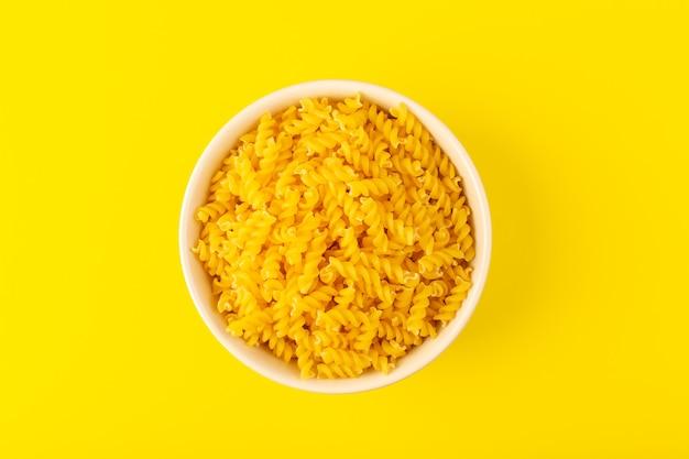 トップビューイタリアの乾燥パスタは、黄色の背景のイタリアのスパゲッティ食品パスタに分離されたクリーム色の丸いボウルの中に小さな黄色の生パスタを形成 無料写真
