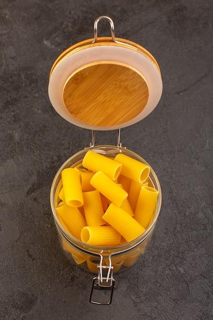 Вид сверху итальянские сухие макароны желтые сырые внутри чаши, изолированных на темном Бесплатные Фотографии