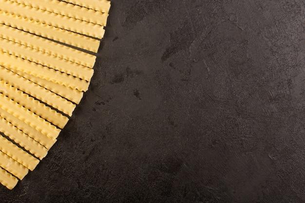 暗い上に並ぶイタリアのロングパスタ生黄色のトップビュー 無料写真