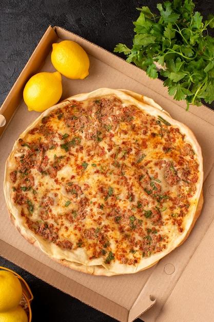Вид сверху тесто lahmacun с рубленым мясом с зеленью и лимоном внутри бумажной коробки вкусная выпечка Бесплатные Фотографии