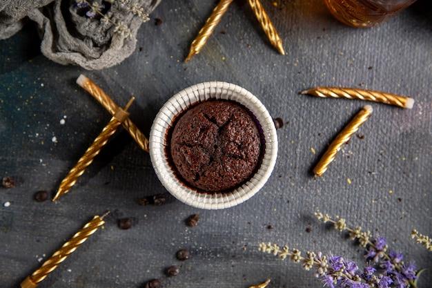 灰色のデスクビスケットクッキーケーキチョコレートティーでキャンドル紫花とお茶のトップビュー小さなチョコケーキ 無料写真