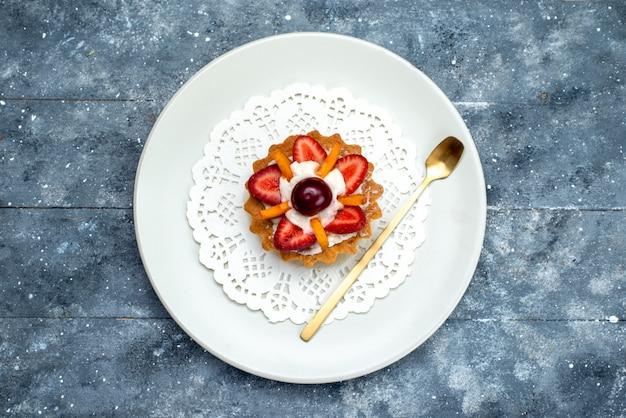 グレーとブルーのデスクフルーツケーキビスケットの白いプレート内のクリームとフルーツの小さなおいしいケーキのトップビュー 無料写真