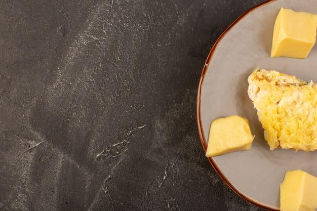 灰色の机の上の鶏の内部とフレッシュチーズの内部プレートとマヨネーズ野菜のサラダ 無料写真