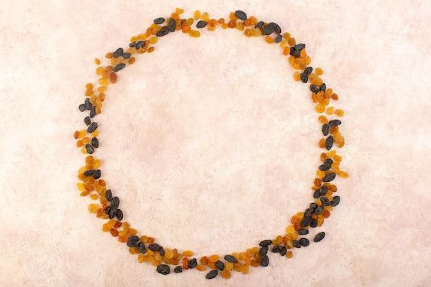 Вид сверху апельсиновый сушеный изюм с черными сухофруктами, формирующий круг на розовом Бесплатные Фотографии