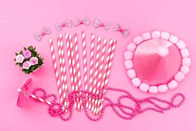 Вид сверху розово-белые конфеты в виде палочки вместе с шапочкой на день рождения милый розовый, бантики на розовом, цвет дня рождения Бесплатные Фотографии