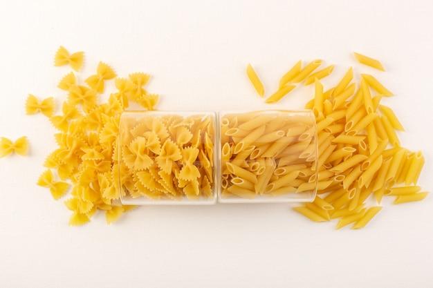 トップビュー生パスタ乾燥イタリアンイエローパスタ透明なプラスチック製のボウルの内側と白い背景のイタリア料理の食事に広がる 無料写真