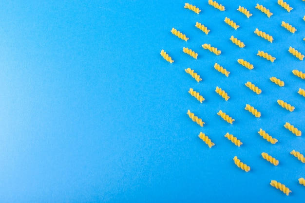 トップビュー生黄色パスタ分離された青い背景食品食事スパゲッティに並ぶ乾燥イタリアンパスタ 無料写真
