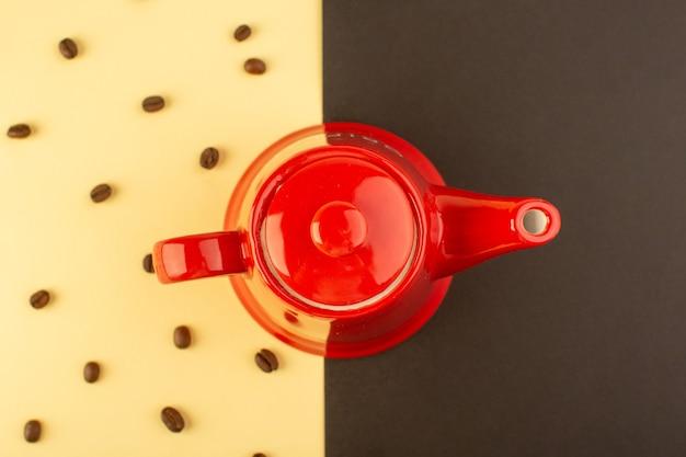 黄褐色のテーブルに茶色のコーヒーの種子を上から見る赤いやかん 無料写真